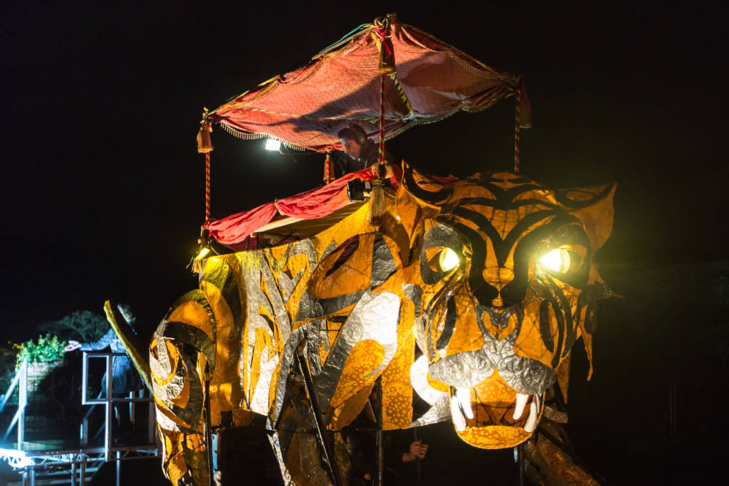 DJ performing on stage set atop a glowing lantern in the shape of a bengal tiger