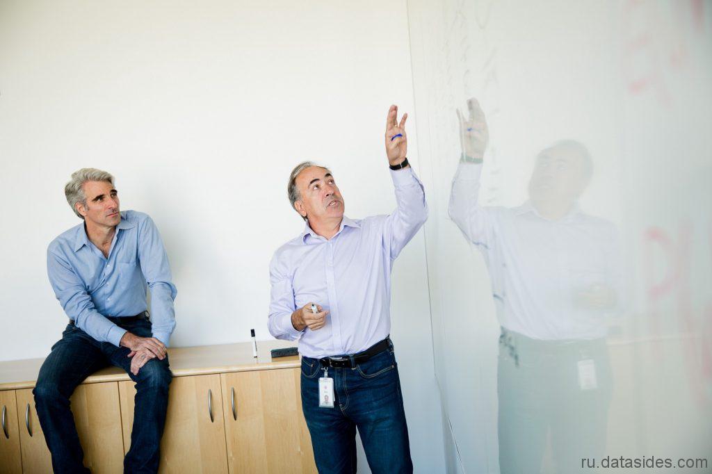 Старший вице-президент по разработке программного обеспечения Крейг Федериги (слева) слушает руководителя команды обработки голоса Siri Алекса Эйсеро в штаб-квартире Apple