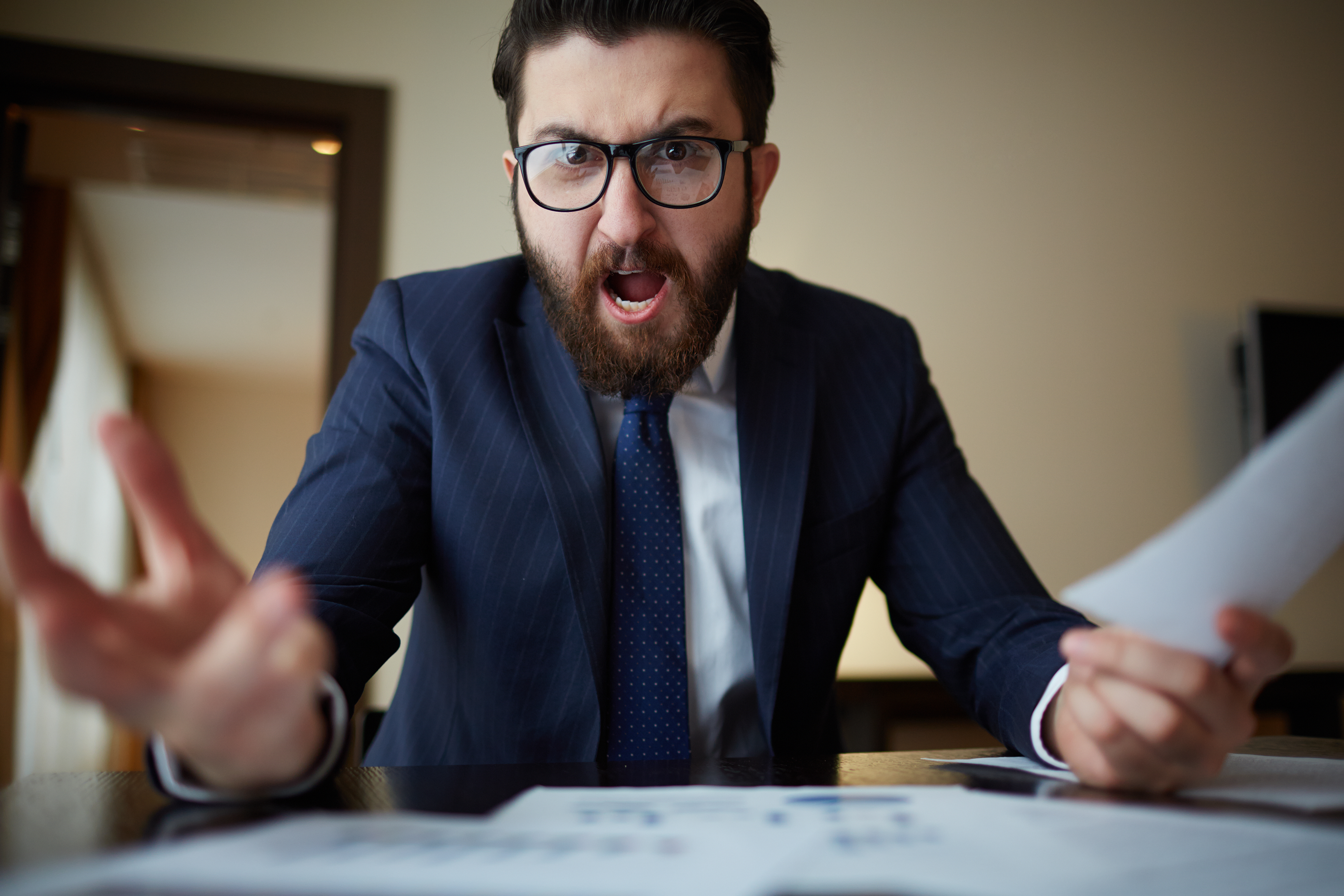 Angry businessman with document shouting at somebody