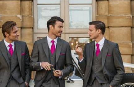 three men in dark grey suits with magenta ties