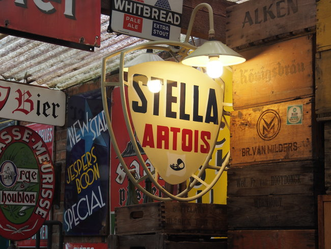 old brand sale signs, focus on yellow Stella Artois sign