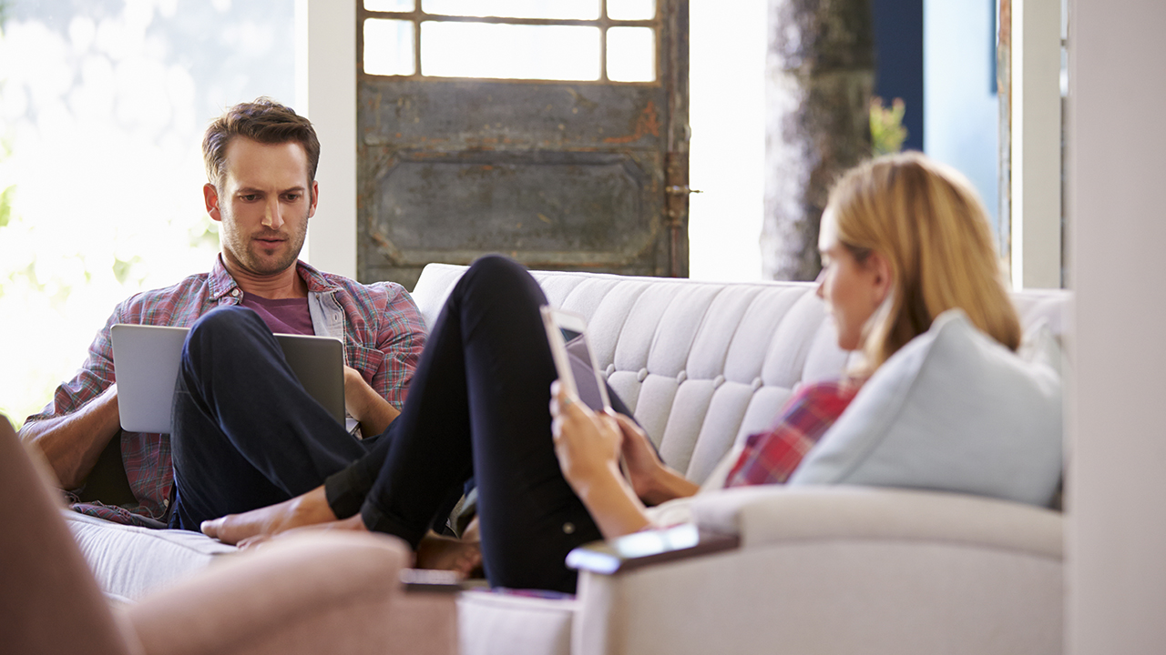 Couple At Home On Sofa In Lounge Using Digital Devices