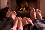 Family of feet warming at a fireplace