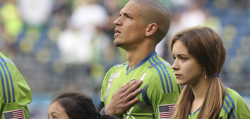 SEATTLE, WA - JUNE 20:  Osvaldo Alonso #6 of the Seattle Sounders stands at attention during the national anthem prior to the match against Sporting Kansas City at CenturyLink Field on June 20, 2012 in Seattle, Washington. Alonso recently became a citizen of the United States. The Sounders and Sporting Kansas City played to a 1-1 draw.(Photo by Otto Greule Jr/Getty Images) *** Local Caption *** Osvaldo Alonso