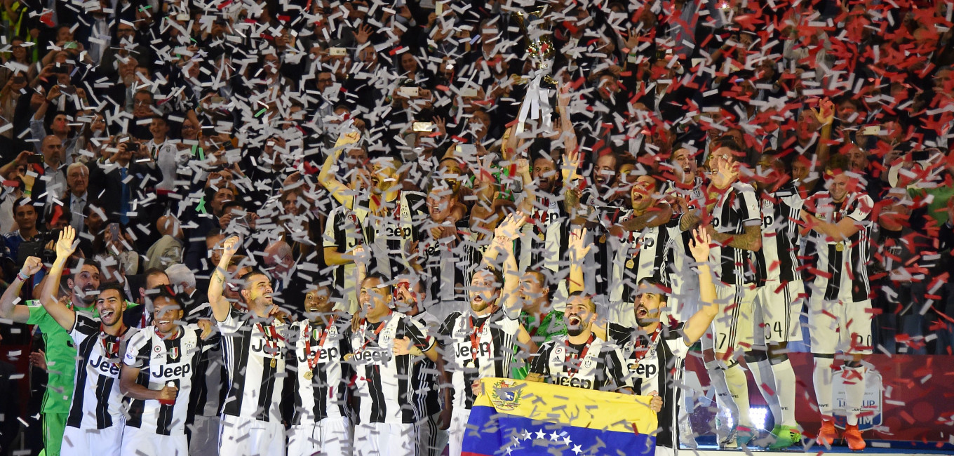 TOPSHOT - Juventus' players celebrate after winning the Italian Tim Cup final on May 17, 2017 at the Olympic stadium in Rome. Dani Alves and Leonardo Bonucci struck one apiece as treble-chasing Juventus secured a third successive Italian Cup with a 2-0 victory over Lazio at the Stadio Olimpico today.   Juventus, who won a league and Cup double the past two seasons, can clinch a record sixth consecutive Serie A title -- and a record third successive double -- with victory at home to Crotone in their penultimate Serie A game of the season on Sunday.  / AFP PHOTO / Andreas SOLARO        (Photo credit should read ANDREAS SOLARO/AFP/Getty Images)