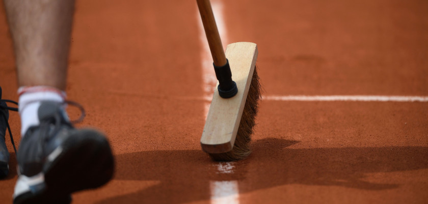 A worker sweeps a line on the Suzanne Lenglen court during the Roland Garros 2017 French Open on May 29, 2017 in Paris.  / AFP PHOTO / Lionel BONAVENTURE        (Photo credit should read LIONEL BONAVENTURE/AFP/Getty Images)