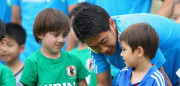 CLEARWATER, FL - JUNE 03:  Shinji Kagawa speaks to a local boy as he waits with the Japan squad to pose for pictures with children from the local area during a Japan training session at North Greenwood Recreation & Aquatic Complex on June 3, 2014 in Clearwater, Florida.  (Photo by Mark Kolbe/Getty Images)