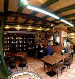 La taverna d'en Pep en Barcelona Comedor de la entrada, con la estantera de vinos al fondo.