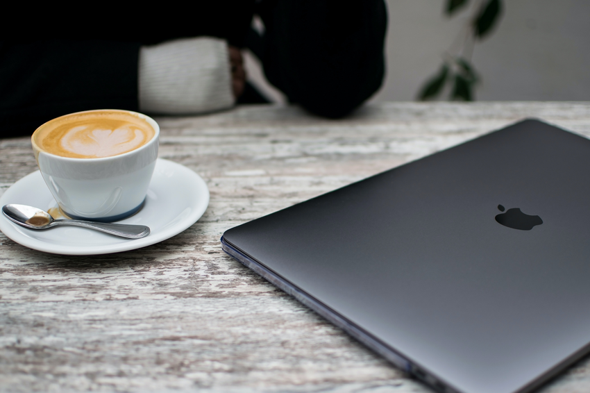 image of a laptop on a desk with a coffee cup