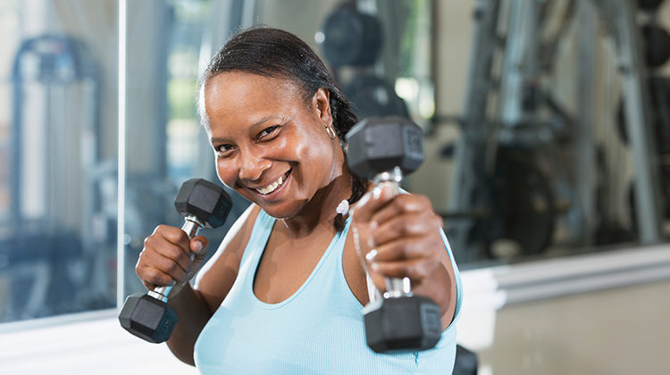 Mature woman in health club, lifting weights.