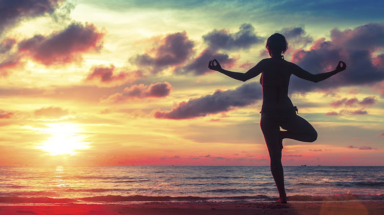 Silhouette young woman practicing yoga on the beach at surrealistic sunset. Healthy lifestyle choices.