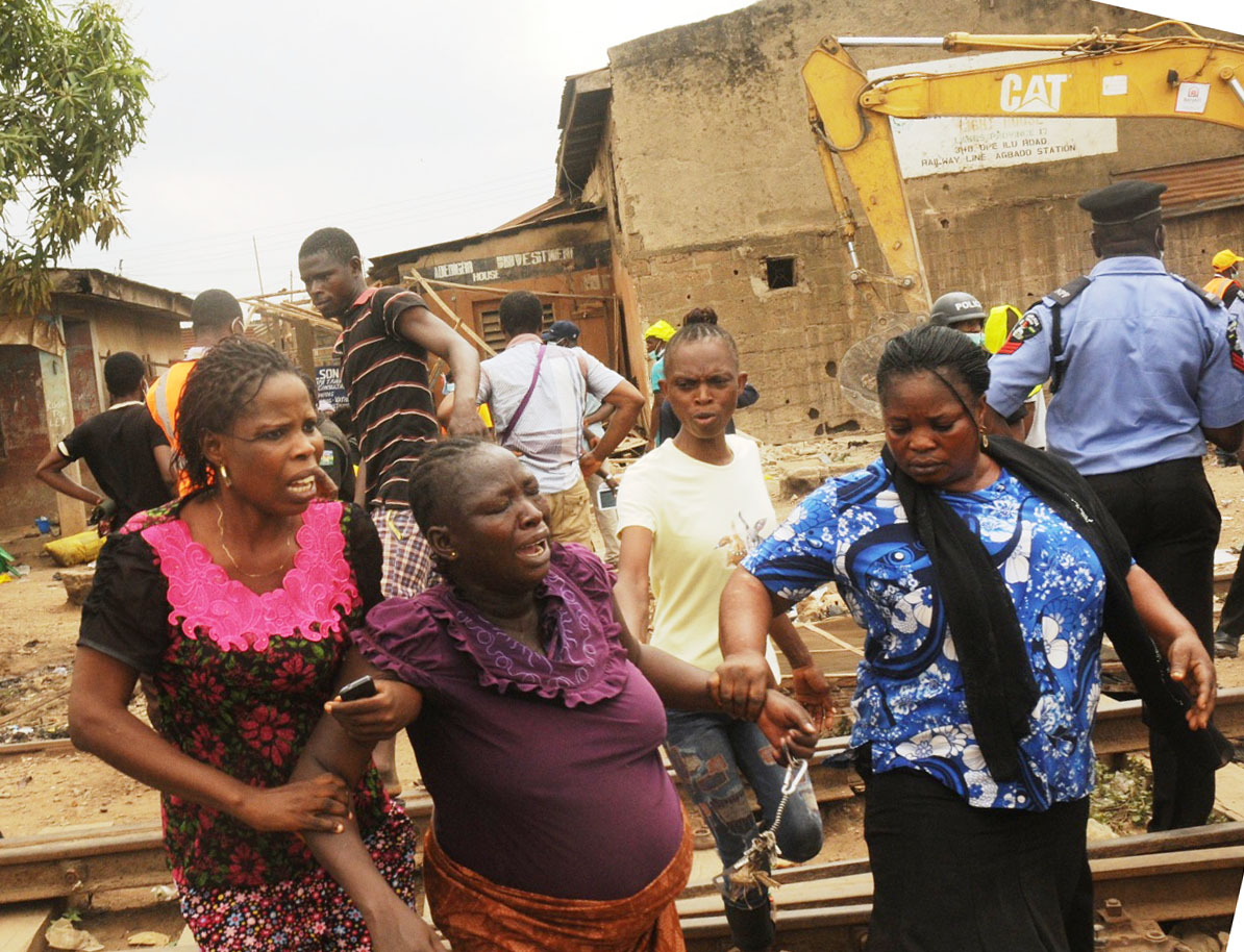 Pregnant woman being assisted out during the demolition of houses