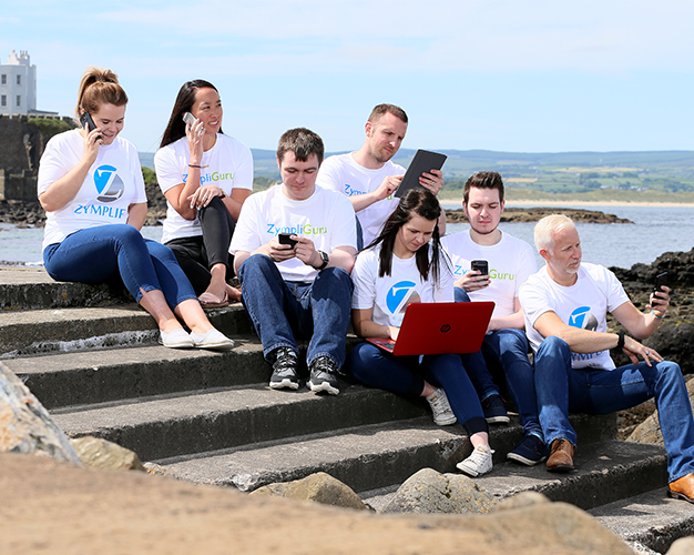 Seven Zymplify Guru's all working on laptops and smart phones, sitting on steps outside in the sunshine.