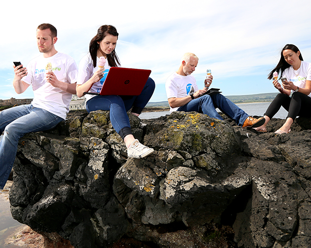 Zymplify Gurus sitting on rocks working on laptops and eating ice-cream