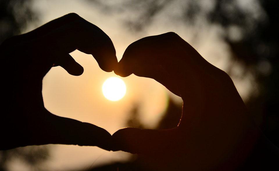 Unes mans fent la forma de cor durant la posta de sol
