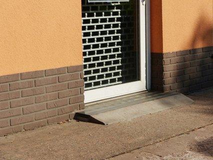 An einer Eingangstür wird ein Höhenunterschied von etwa sechs Zentimetern mit einer kurzen Schräge angeglichen.