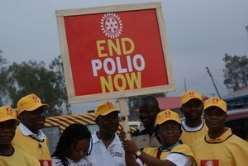 Volunteers hold an End Polio Now banner