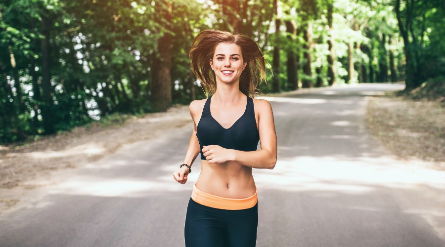 Sporty young fitness girl running and listening music in the park