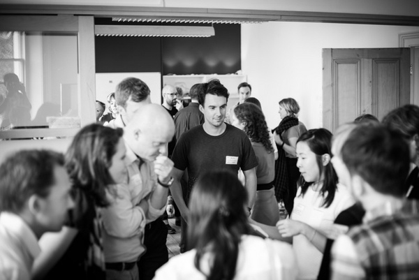 A crowd of workshop attendees talking to each other