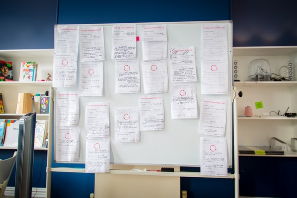 Whiteboard covered in completed worksheets