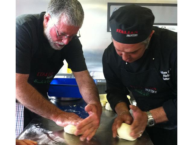 Matteo Rao teaching pizza dough rolling during a cooking class