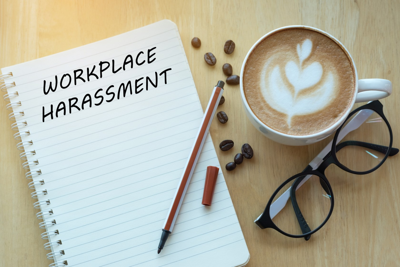 Workplace harassment concept on notebook with glasses, pencil and coffee cup on wooden table. Business concept.