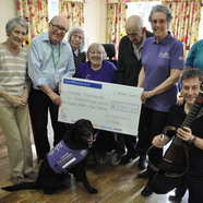 Mungo at Colten Care's Linden House care home in Lymington with his partner Barbara Houston, seated. Also joining residents and team members are Canine Partners volunteer Liz Downs, standing third from right, and singer and guitarist Nigel Revill.