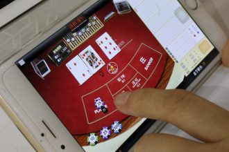 An attendant demonstrates an online baccarat game on a smartphone at the Global Gaming Expo (G2E) Asia in Macau, China May 19, 2015. REUTERS/Bobby Yip - RTX1DL7S