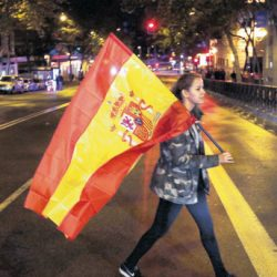 A supporter of the Popular Party carries a Spanish flag as she leaves the party headquarters in Madrid, Sunday, Dec. 20, 2015. A strong showing Sunday by a pair of upstart parties in Spain's general election upended the country's traditional two-party system, with the ruling Popular Party winning the most votes but falling far short of a parliamentary majority and at risk of being booted from power.(AP Photo/Emilio Morenatti)