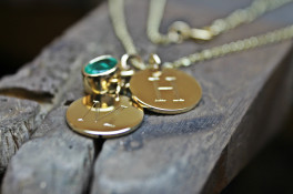9K GOLD DISC PENDANTS WITH A 1.19CT OVAL EMERALD