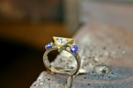 triangular setting with a brilliant cut diamond & sapphires