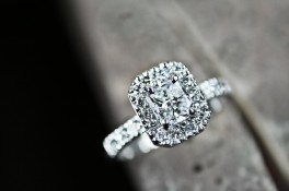 A CUSHION CUT HALO STYLE DIAMOND RING WITH SHOULDERS SET