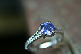 BRILLIANT CUT SAPPHIRE WITH GRAIN SET DIAMOND SHOULDERS