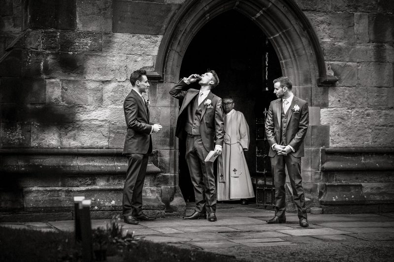 Groomsmen outside church drinking from hip flask