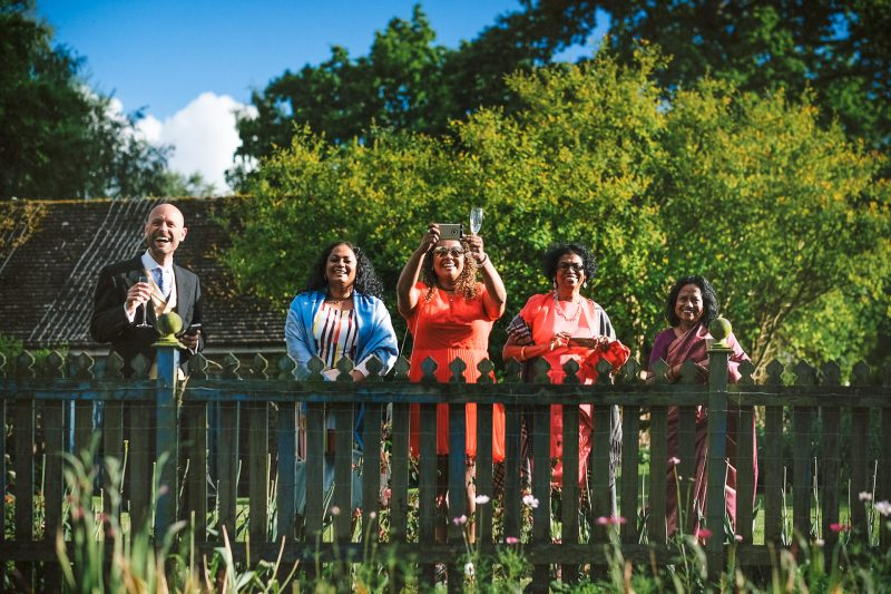 Guests with cameras out at a relaxed Surrey garden wedding