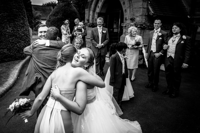 Bride and Groom hug their friends at the church after getting married