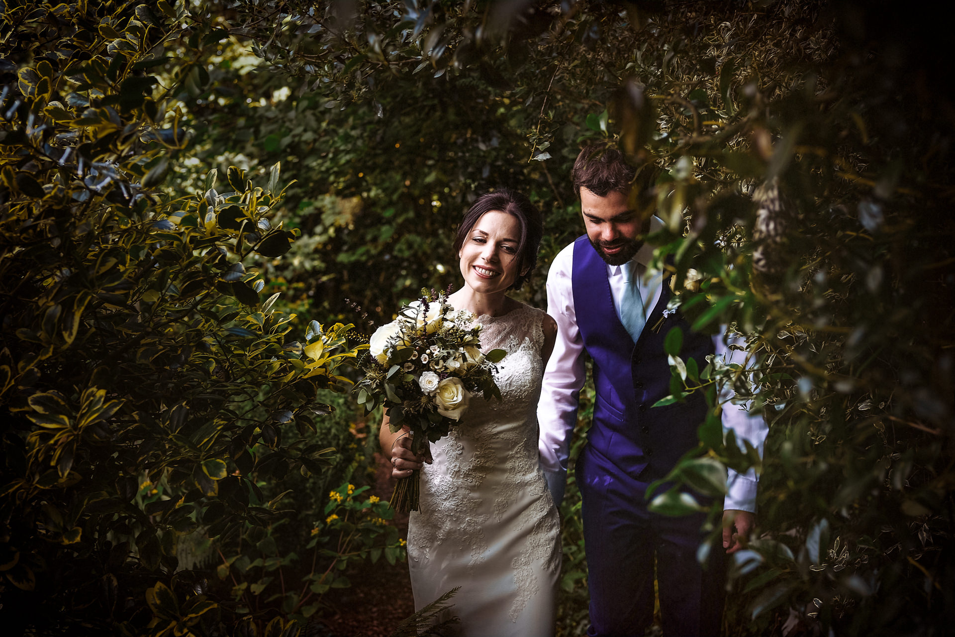 Bride and groom walking through the bushes at a back garden wedding in Suffolk