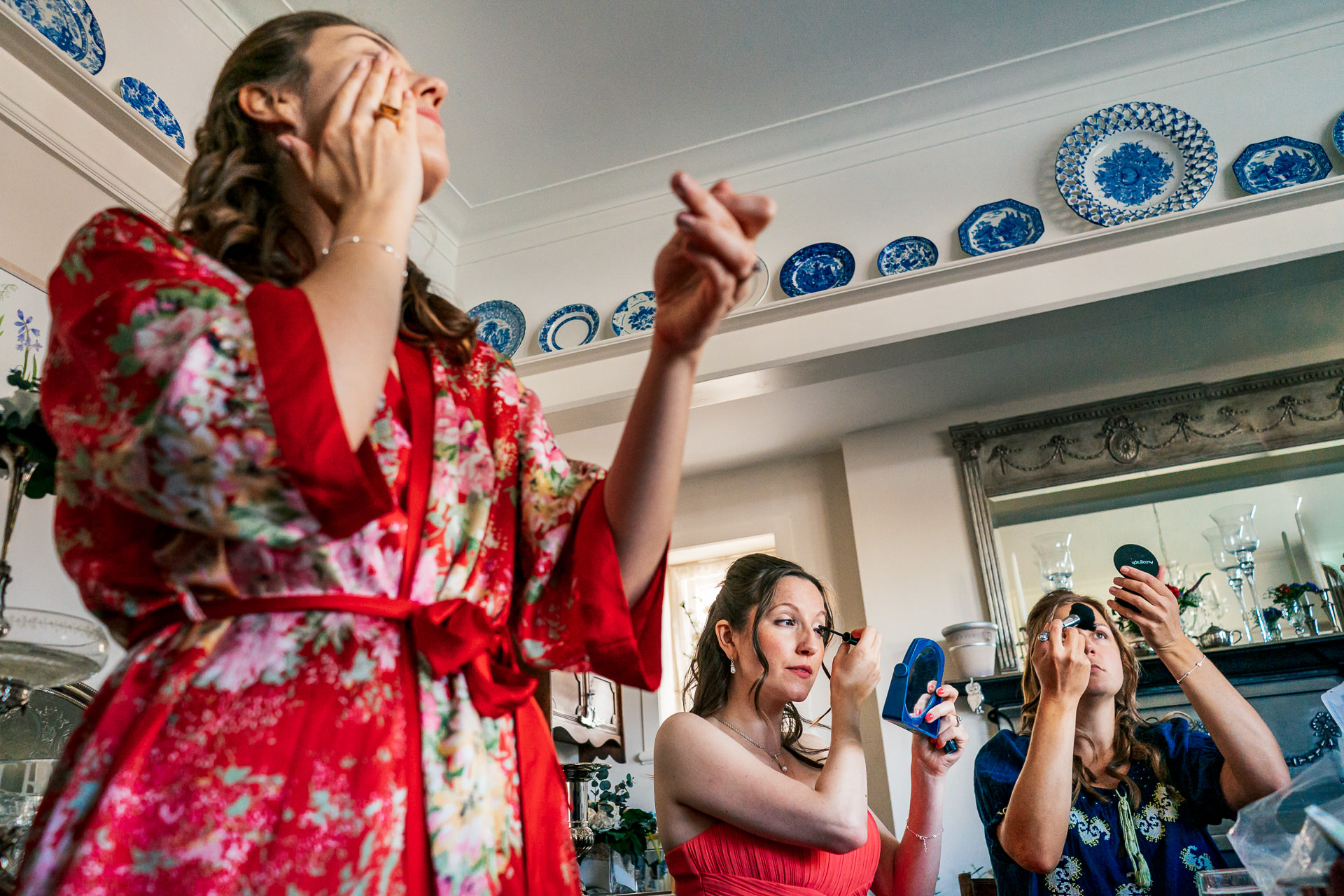 Bridesmaids putting on makeup at the family home
