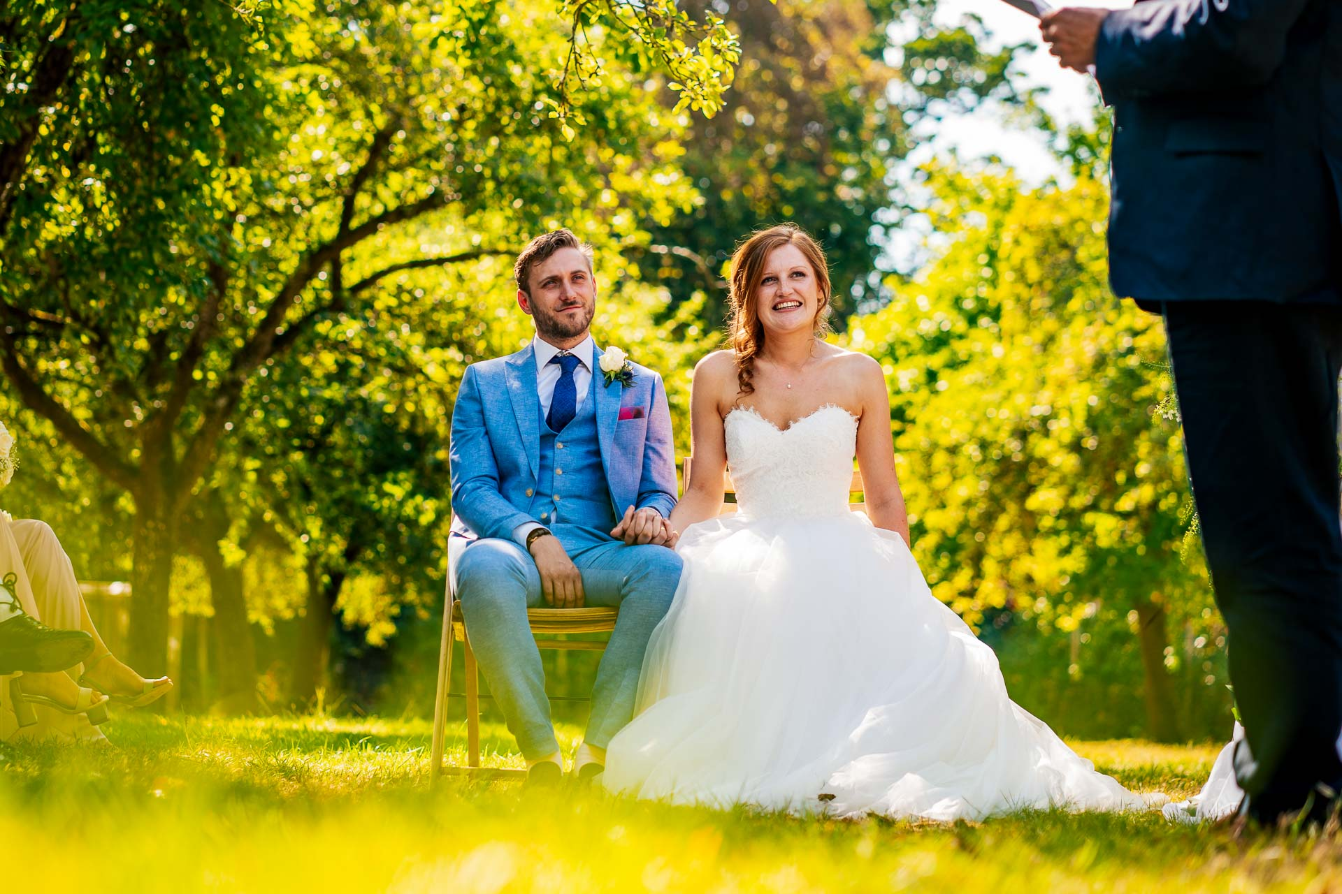 Bride and groom sitting in the orchard at Sparkford Hall wedding in Somerset