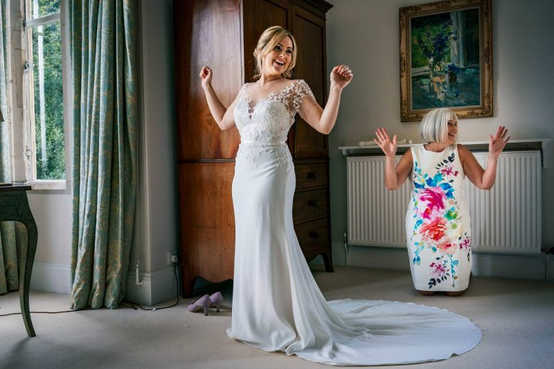 Bride getting into her dress at Matara Centre wedding in Gloucestershire