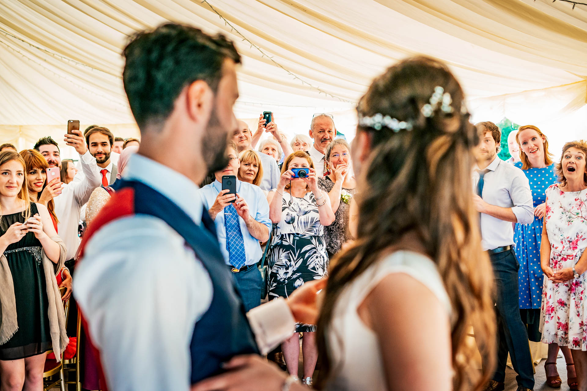 Guests cheering during bride and groom first dance