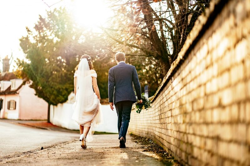 Bride and groom walking in warm evening sunshine at Cambridgeshire Village Hall wedding