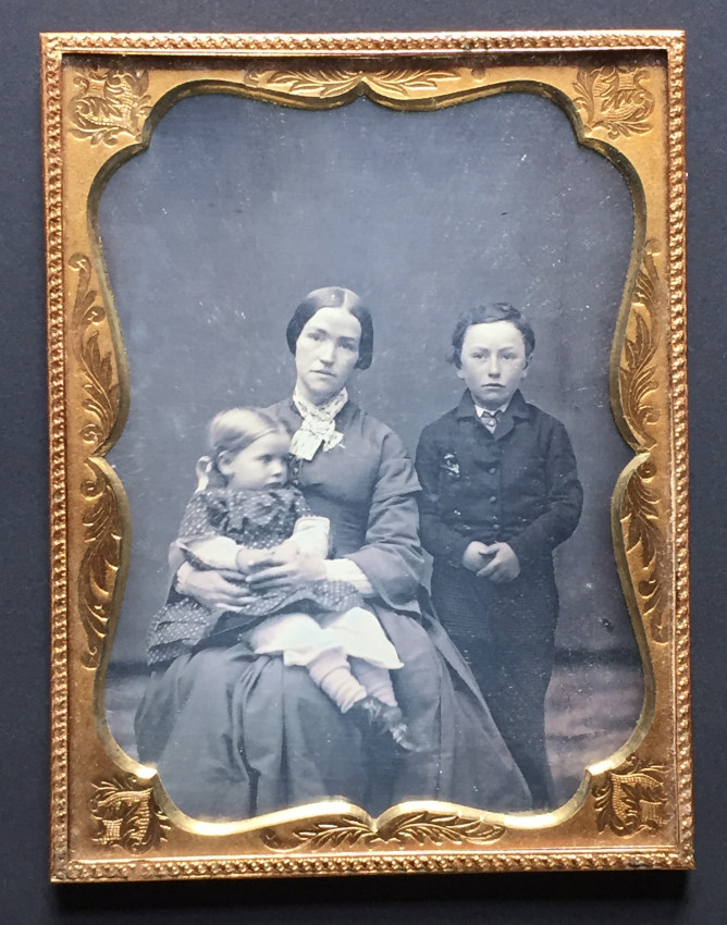 A portrait of a mother and two children