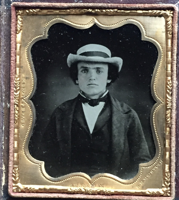 Portrait of young man in white hat.