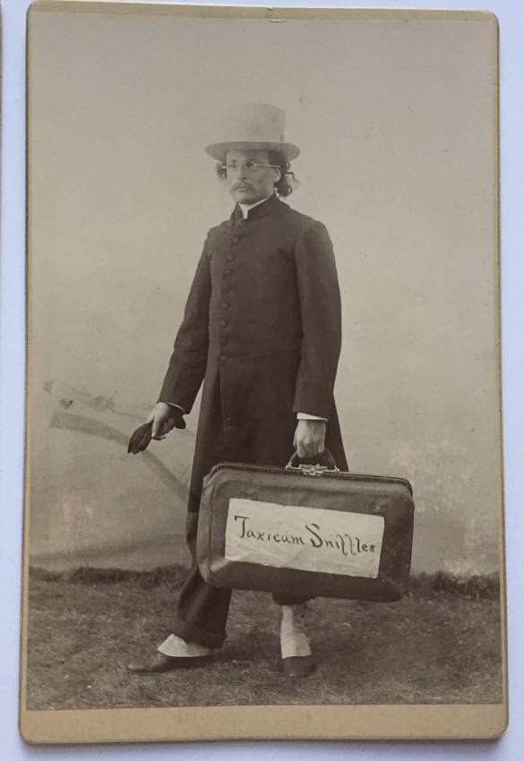 Taxicum Sniffler, man posing with suitcase, young girl smartly dressed holding an umbrella