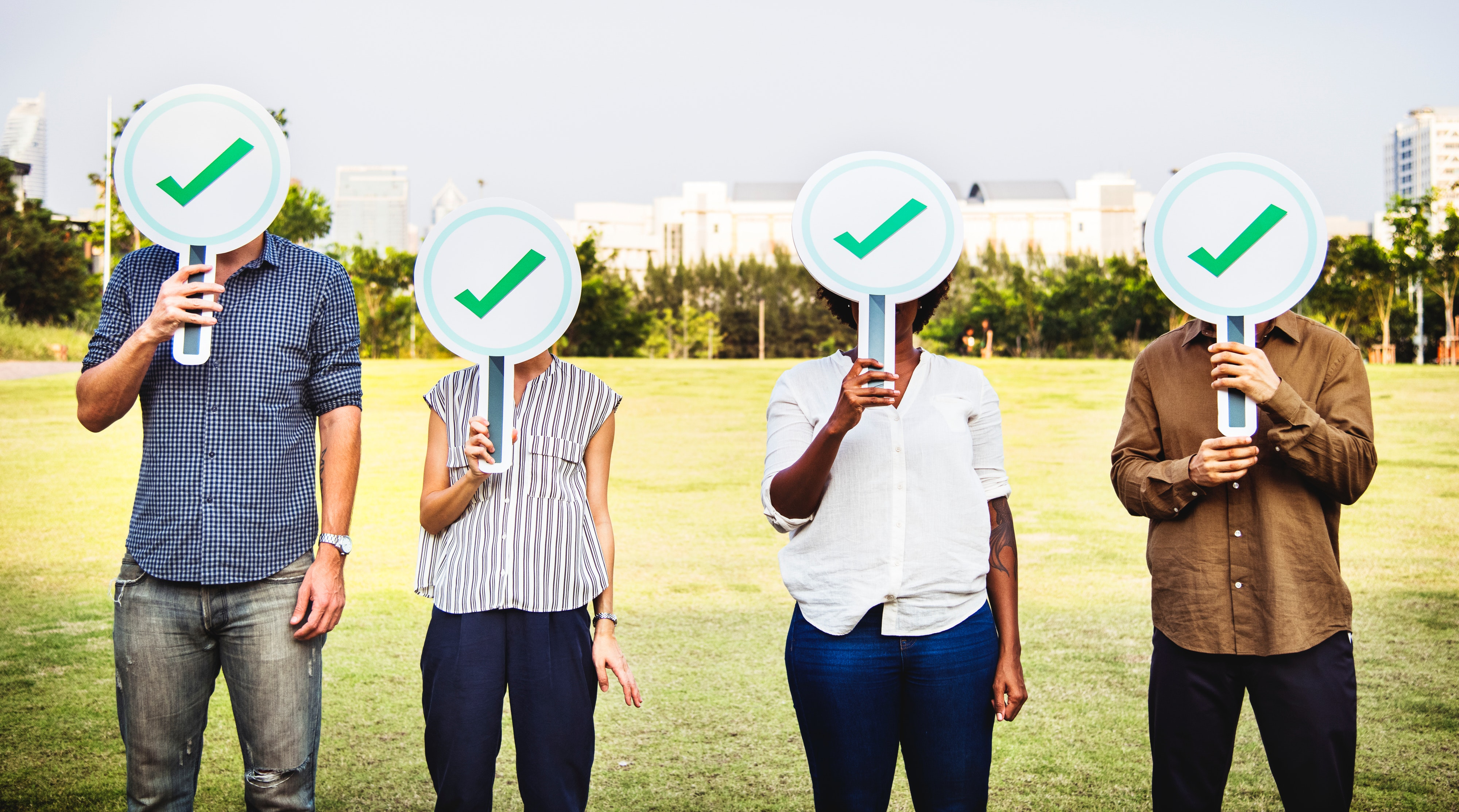 Four people lined up in a field, each with a sign displaying a green tick in front of their face.