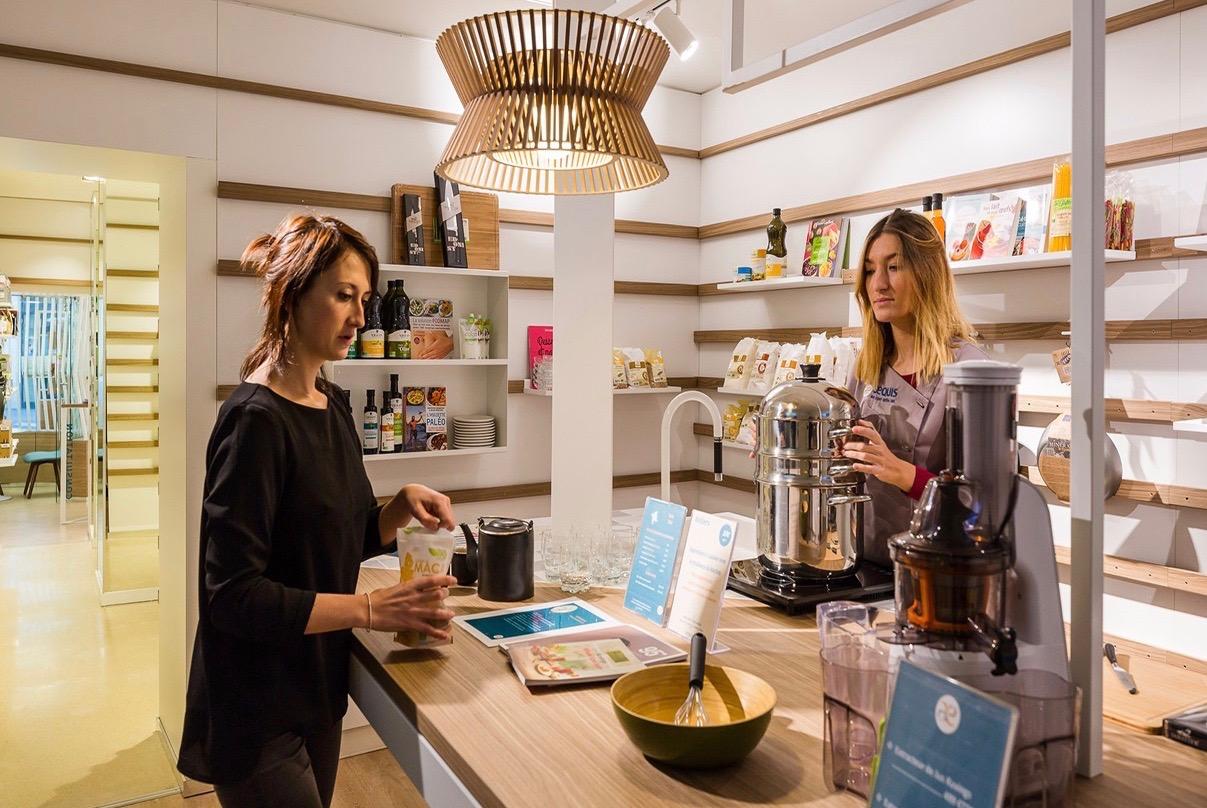 Deux femmes préparent de la vinaigrette à une table à la Boutique Aequis Paris