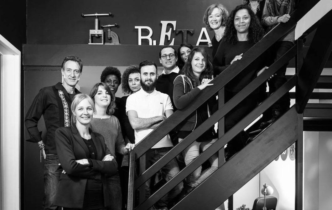 L'équipe de l'agence Retail 3D dans l'escalier de l'agence devant un panneau Retail