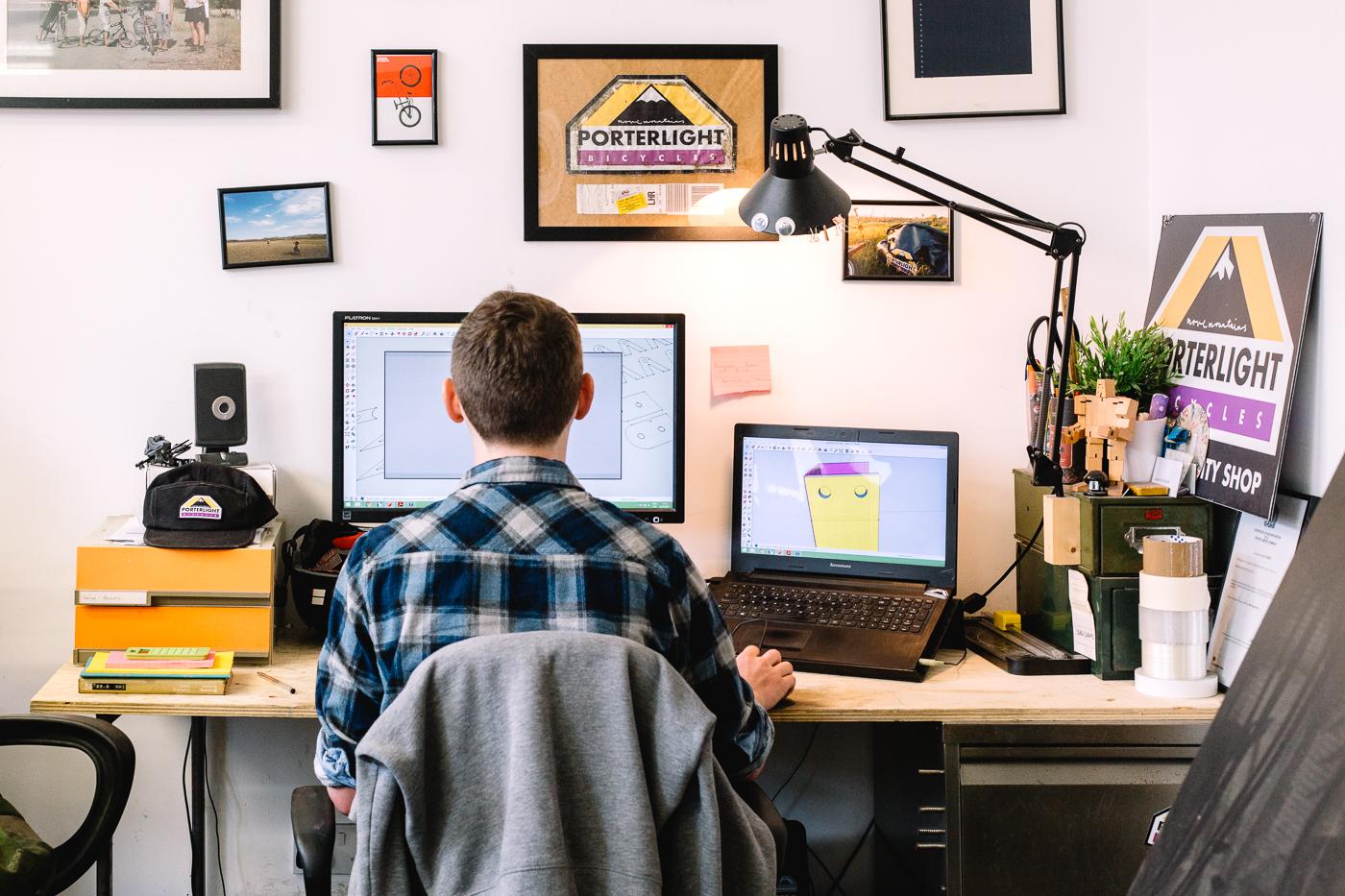 Lawrence Brand à son bureau, devant son ordinateur, entouré de photos de son voyage et de panneaux Porterlight Bicycles