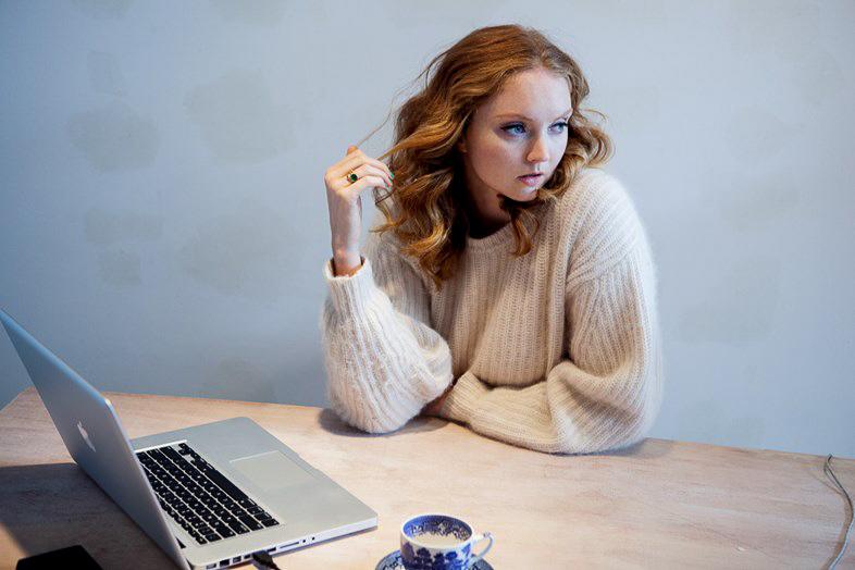 Lily Cole, devant un ordinateur et une tasse de thé, regarde sur le côté